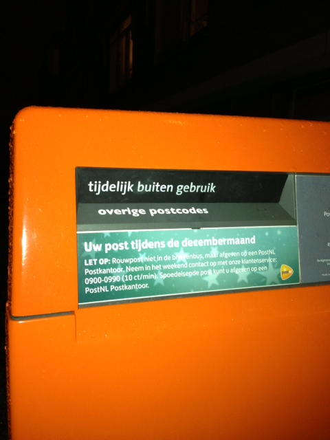 """tidelijk buiten gebruik"" - temporarily out of service. The black part is covering the slot where the mail usually goes, but the post office does not like people shoving lit fireworks into their post office boxes. Mail resumes tomorrow on the 2nd."