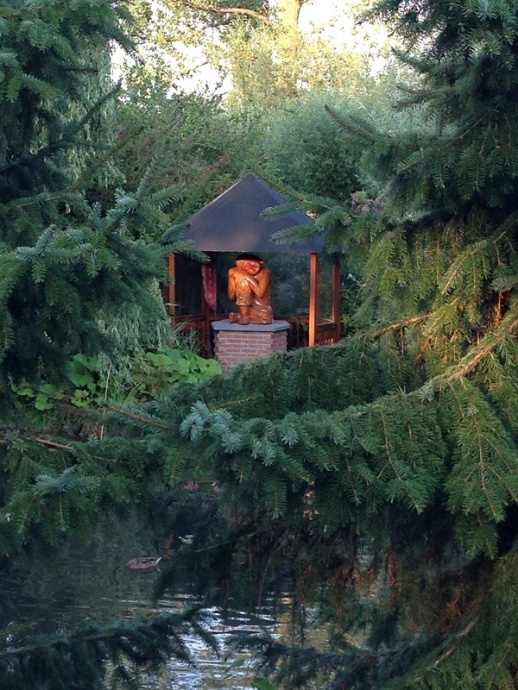 Buddha statue through pine trees